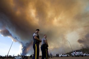 Police officers direct traffic under a cloud of smoke from a wildfire in Fort McMurray, Alberta, Canada on Friday, May 6, 2016. Tens of thousands have been forced from their homes, and the fires are expected to burn for weeks. (Jason Franson/The Canadian Press via AP) MANDATORY CREDIT
